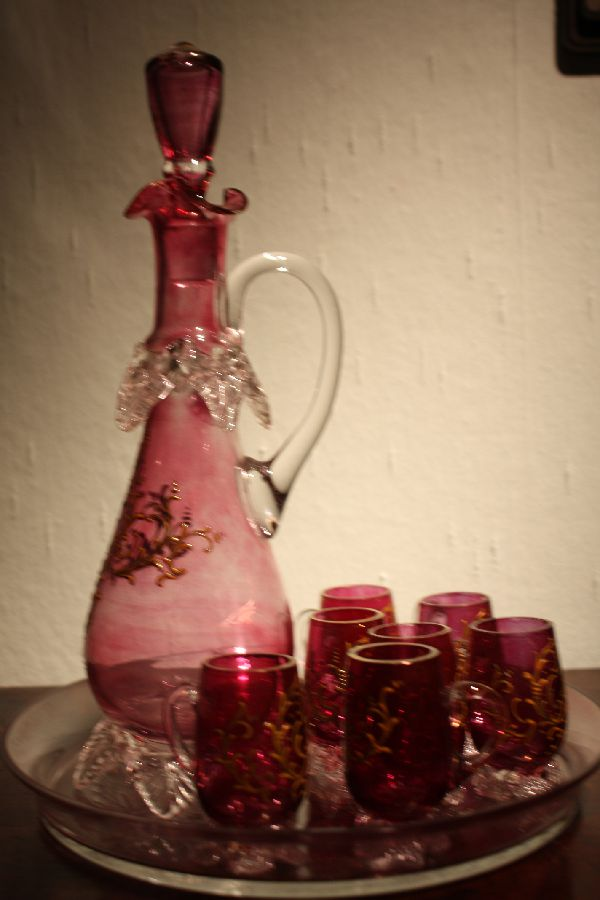 A vintage 1900 Bohemian pink glass liquor pitcher with 7 glasses on a tray