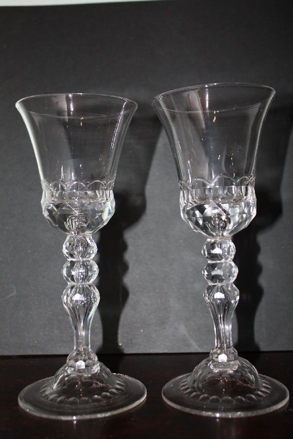 A pair of decorative tall antique 18th century wine glasses