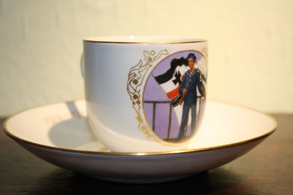 A patriotic porcelain collectable Meissen cup and saucer, sailor in front of the German war flag