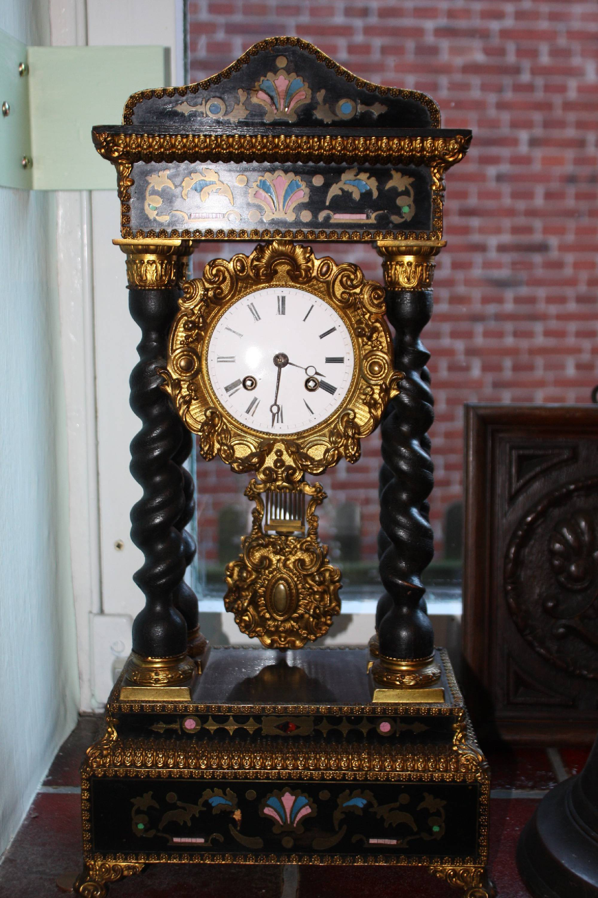 A French ornate antique 19th century mantel clock with four ebonized tortuous pillars and inlays