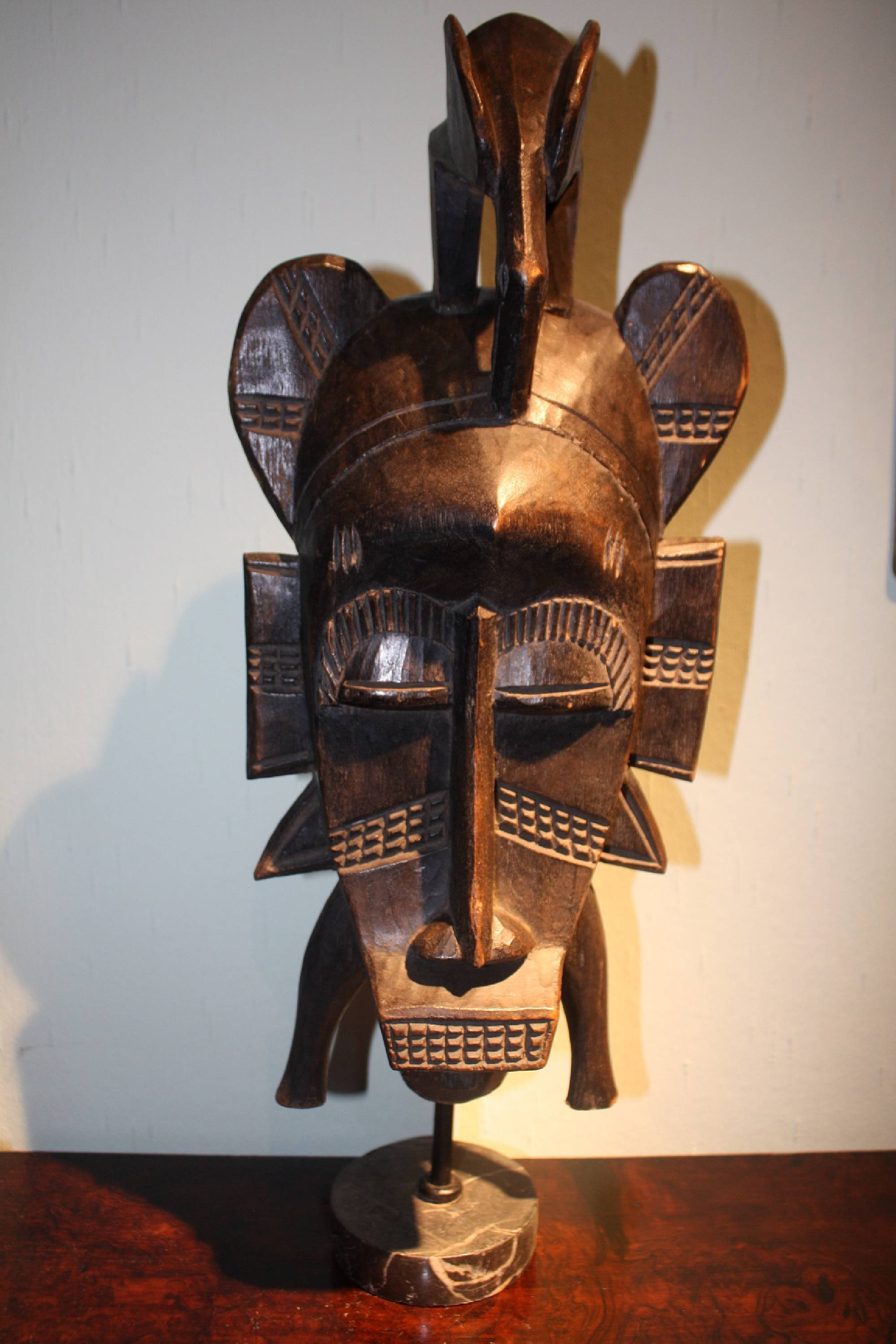 A large West-African handcarved wooden tribal Senufo ritual mask on a grey marble foot